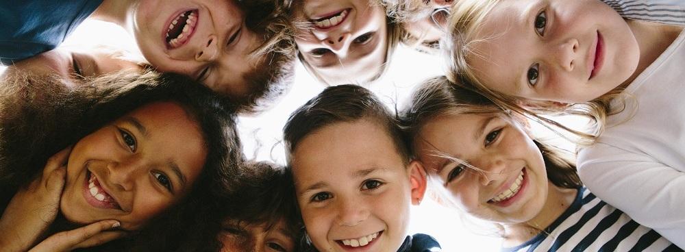 Gesichter von acht Mädchen und Jungen im Kreis