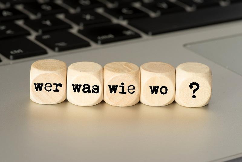 Würfel mit Aufschrift Wer, Was, Wie, Wo, ? auf Tastatur